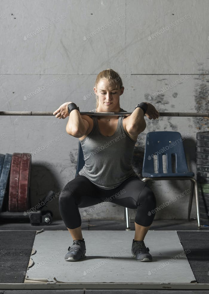 Young female weight lifter training in gym, with copy space.