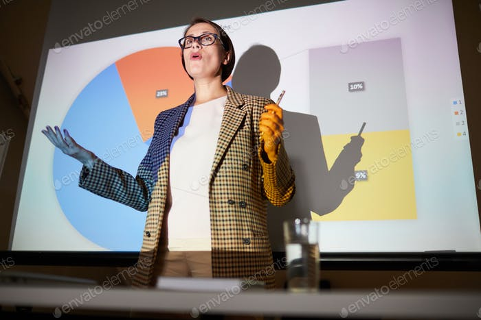 Confident lady explaining data on projection screen