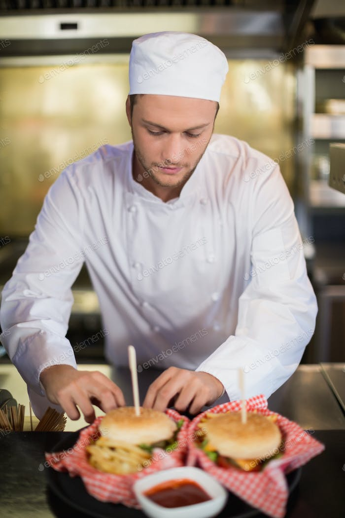 Serious male chef preparing burger in commercial kitchen