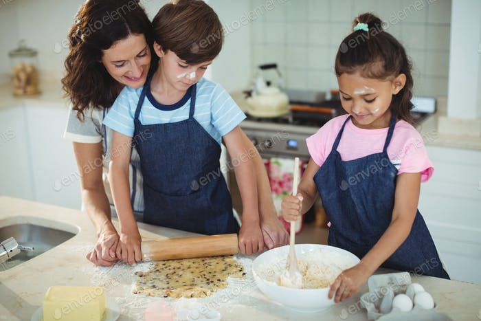 Mother and kids preparing cookies in kitchen
