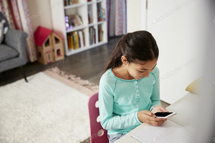 Young Girl Sitting At Desk In Bedroom Using Mobile Phone Whilst Doing Homework