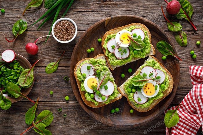 Sandwiches with wholemeal bread, hummus or puree of fresh green peas, radish, cucumber, boiled egg