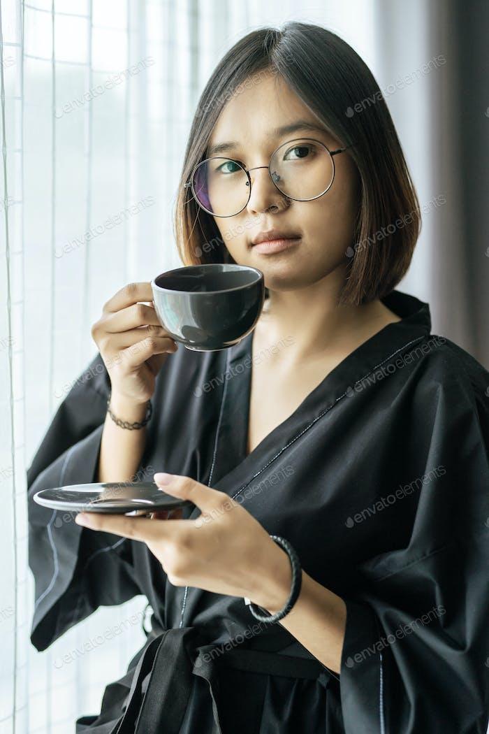 Women wearing black robes, handing coffee in the bedroom.