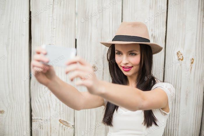 Pretty brunette taking a selfie against bleached wooden planks