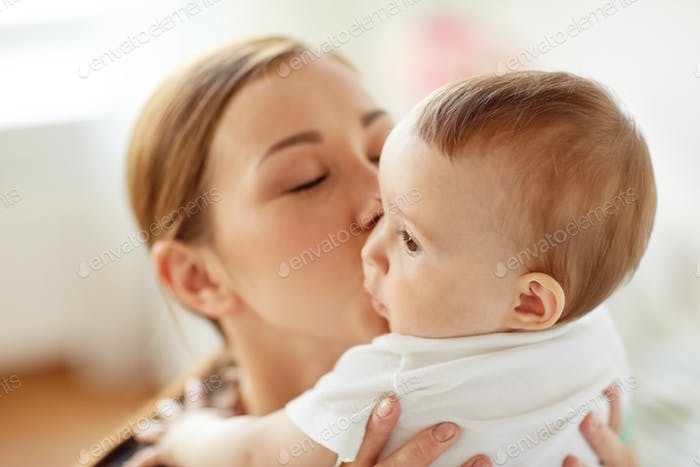 happy young mother kissing little baby at home