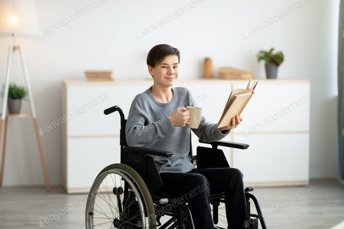 Positive impaired teenager in wheelchair drinking tea and reading interesting book at home