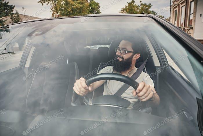 A modern bearded man driving a car