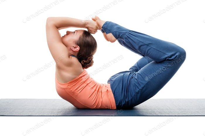 Sporty fit woman practices yoga asana Dhanurasana