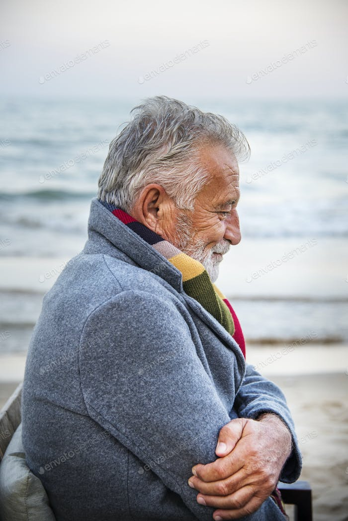 Mature man sitting on a chair by the seashore