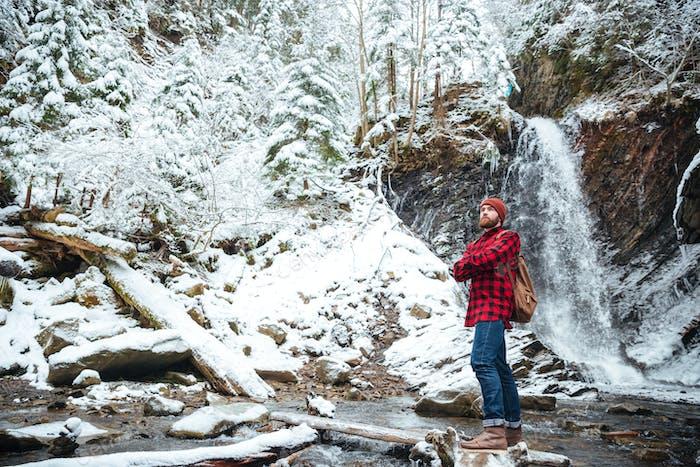 Nachdenklicher bärtiger Mann, der in der Nähe von Wasserfall in Bergen im Winter stampft