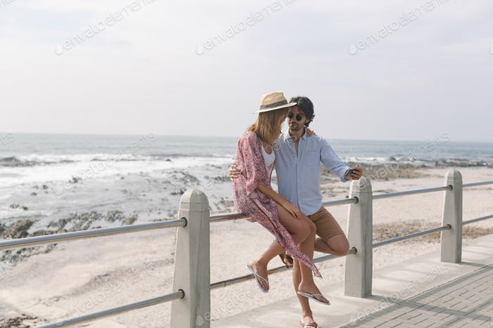 Side view of young Caucasian couple taking selfie while sitting at railing on a sunny day