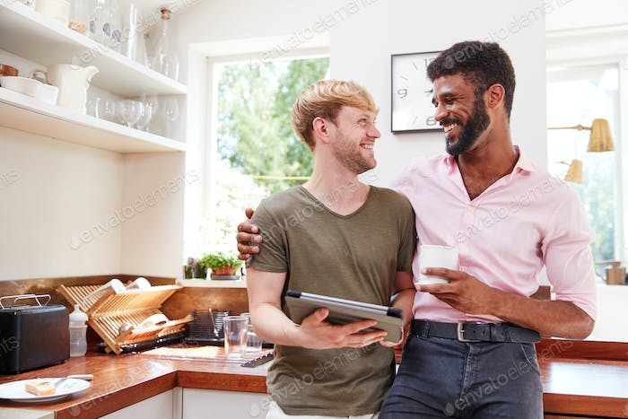 Male Gay Couple Using Digital Tablet At Home In Kitchen Together