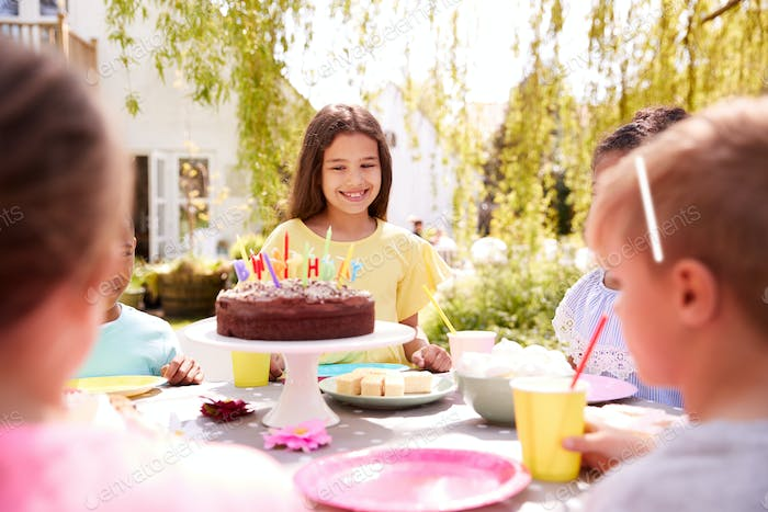 Girl Celebrating Birthday With Friends Having Party In Garden At Home