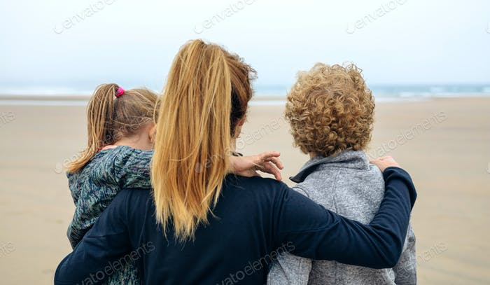 Back view of three generations female looking at sea