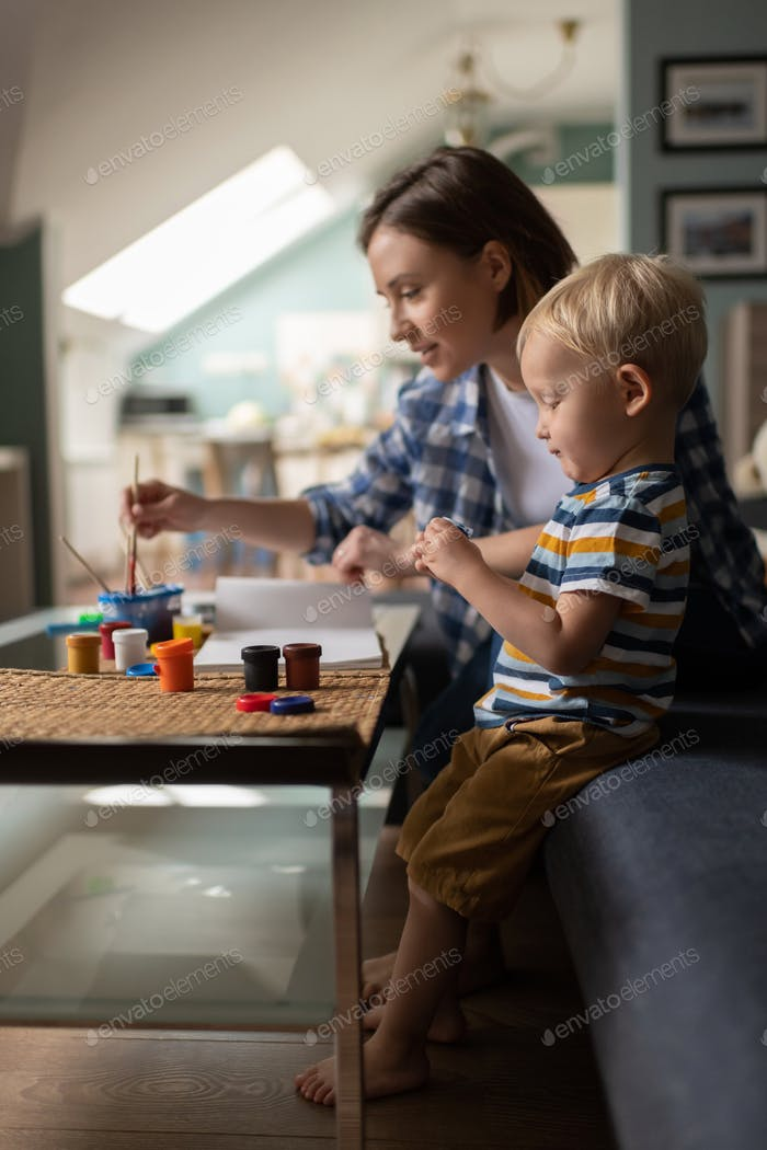 Female babysitter teaching little kid drawing at home