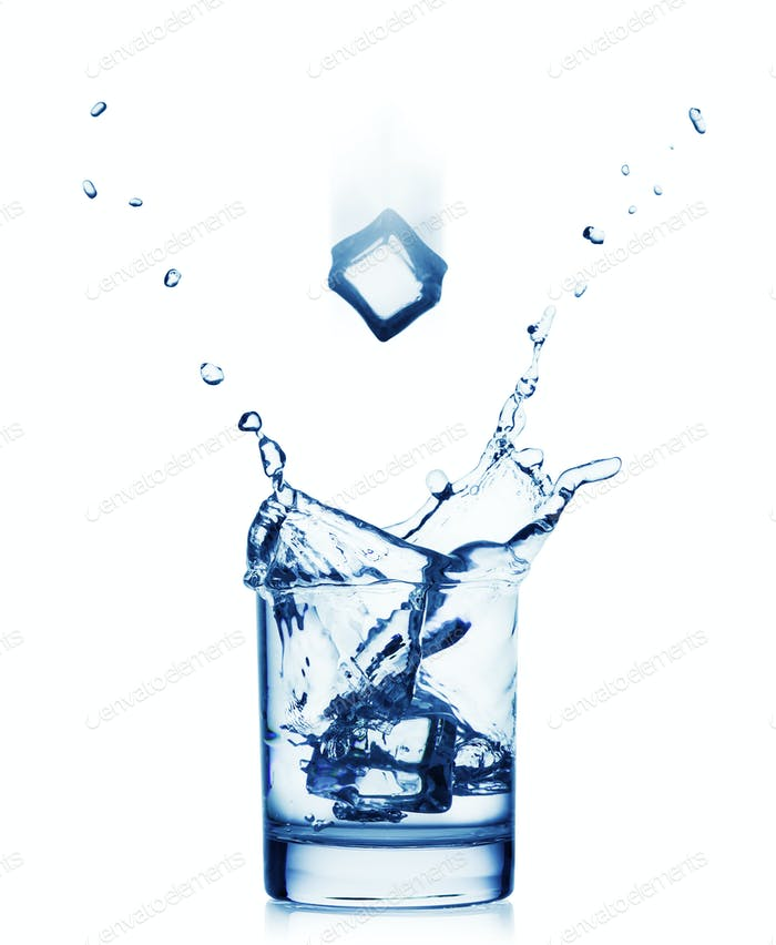 Splash of water in a wide glass with a flying ice