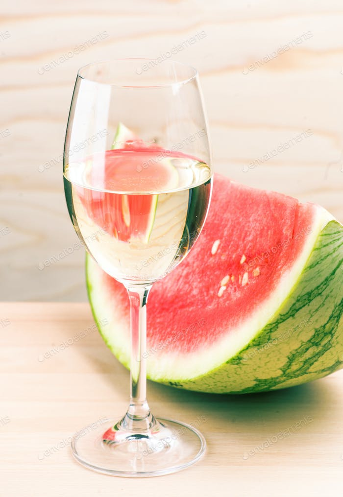 glass of white wine and watermelon on light wood