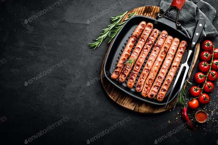 Grilled sausages bratwurst in grill frying-pan on black background. Top view