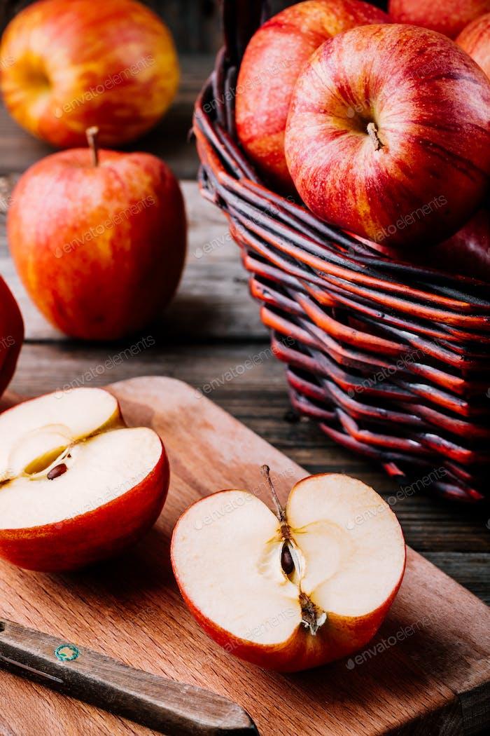 rote reife Äpfel in einem Korb auf einem hölzernen Hintergrund