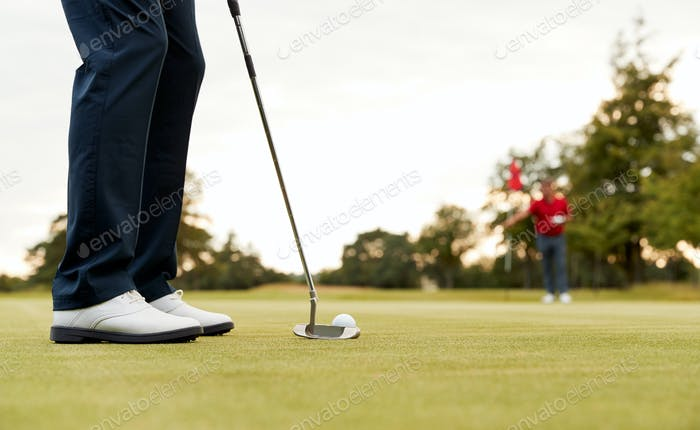 Close Up Of Female Golfer Putting Ball On Green As Man Tends Flag