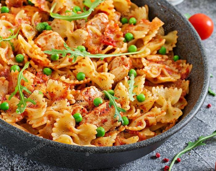 Farfalle pasta with chicken fillet, tomato sauce and green peas. Tasty food. Italian meal