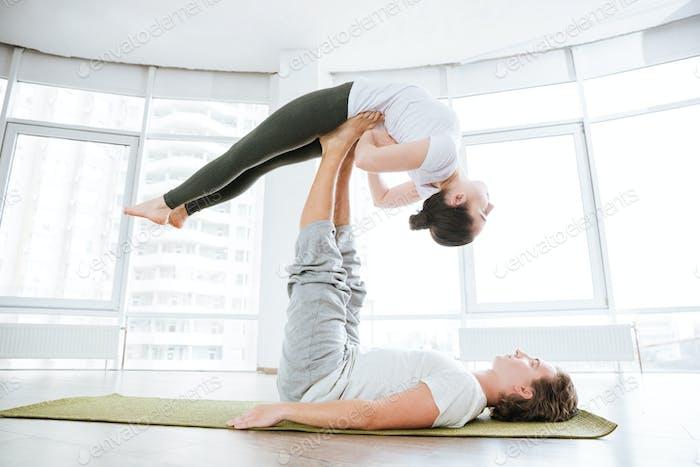 Mujer pacífica practicando acro yoga con pareja