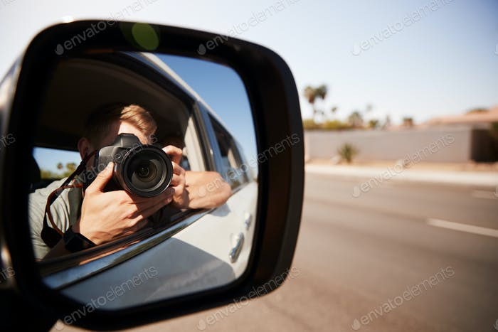 Young man in car taking photo, seen in wing mirror
