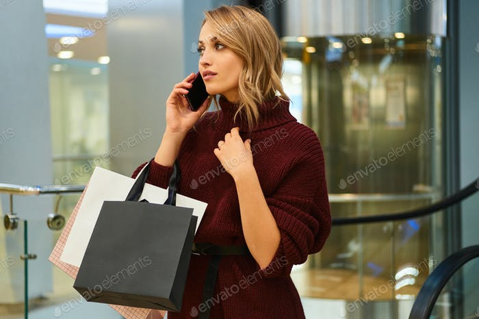 Attractive blond girl in knitted sweater thoughtfully talking on cellphone in shopping mall