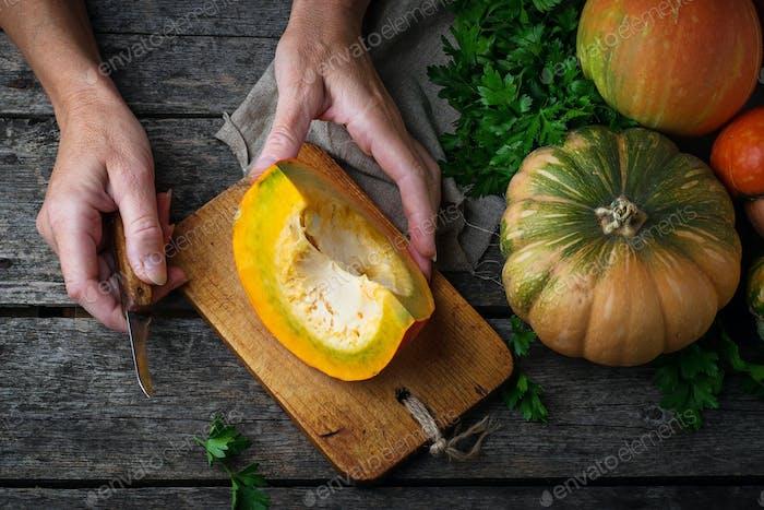 Woman cuts a pumpkin