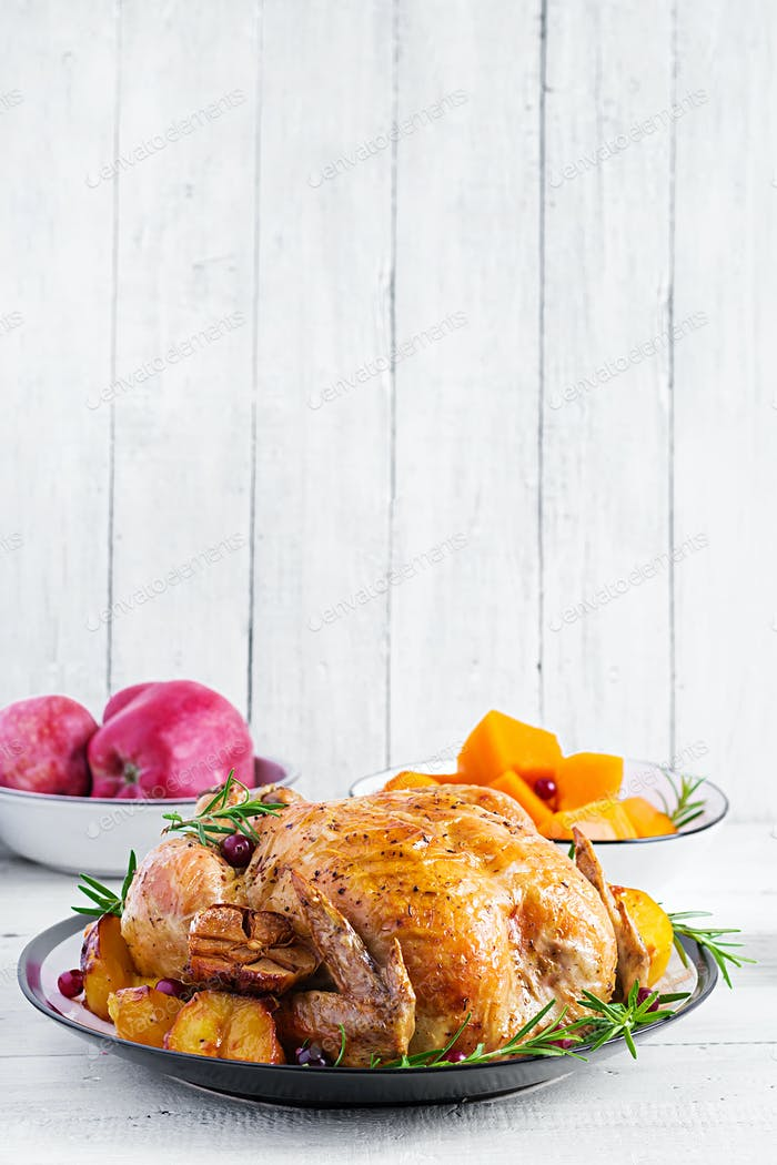 Roasted turkey garnished with cranberries on a rustic style tabl