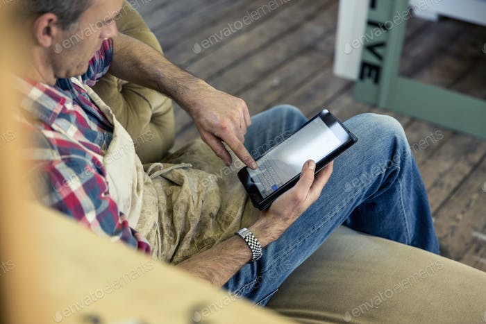 An antique furniture restorer seated looking at a digital tablet in his workshop.