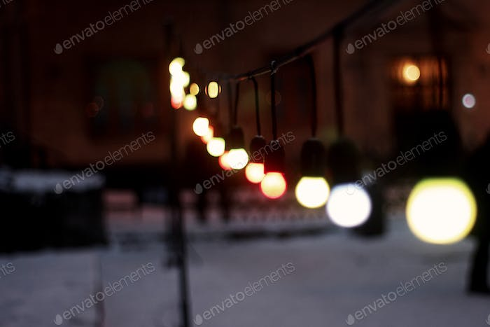 colorful retro garland lights bulbs at street in european city