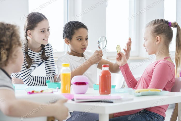 A young boy looking through a magnifying glass and a girl holdin