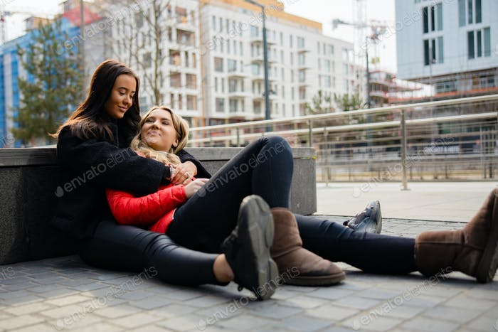 Happy Best Friends Embracing And Sitting On The Ground In City