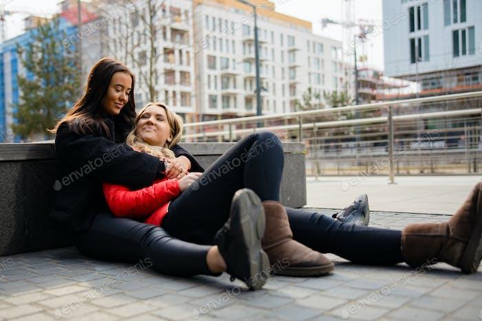 Happy Best Friends Umarmen Und Sitzen Auf Der Erde In der Stadt