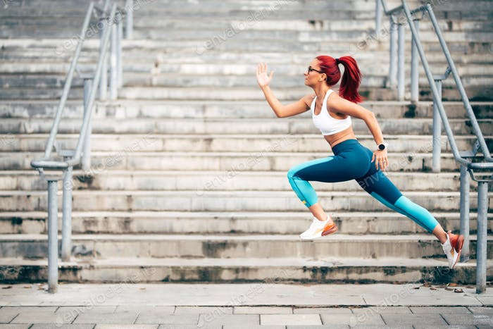 Portrait of woman jumping and running during cardio training