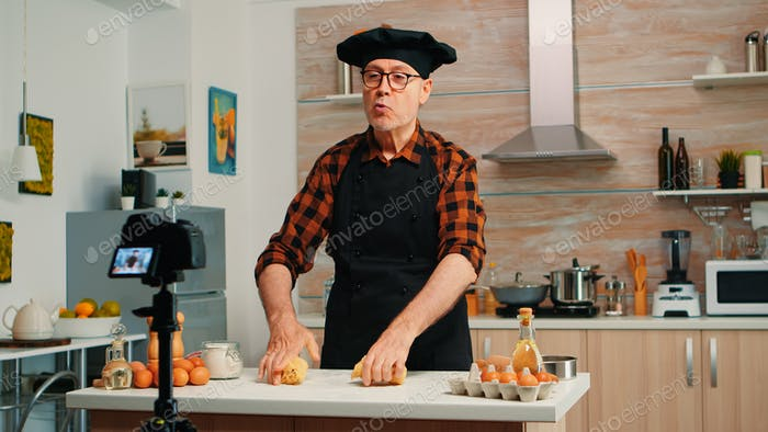 Grandfather recording food video in kitchen