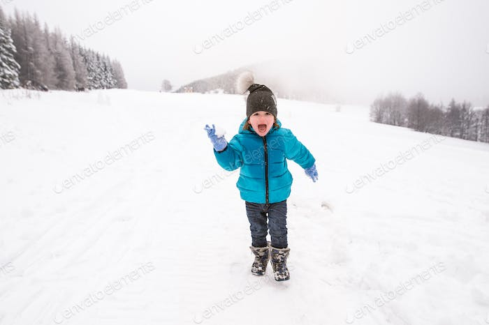 Cute little boy playing outside in winter nature