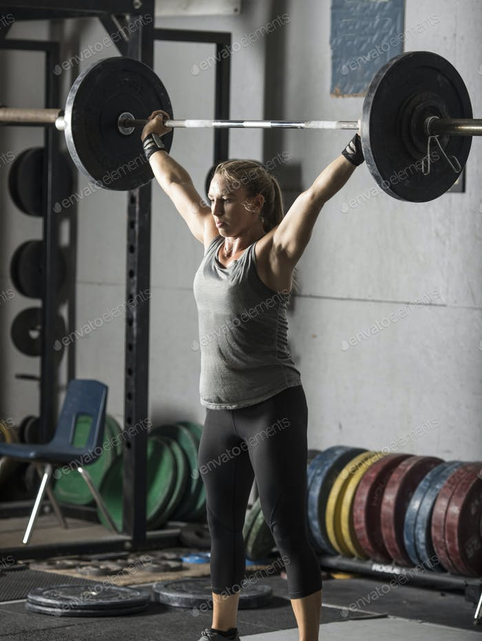 Strong female weight lifter with barbell over her head.