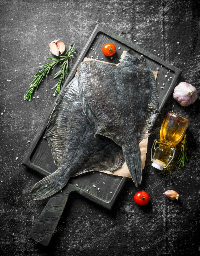Fresh raw flounder on paper with rosemary.