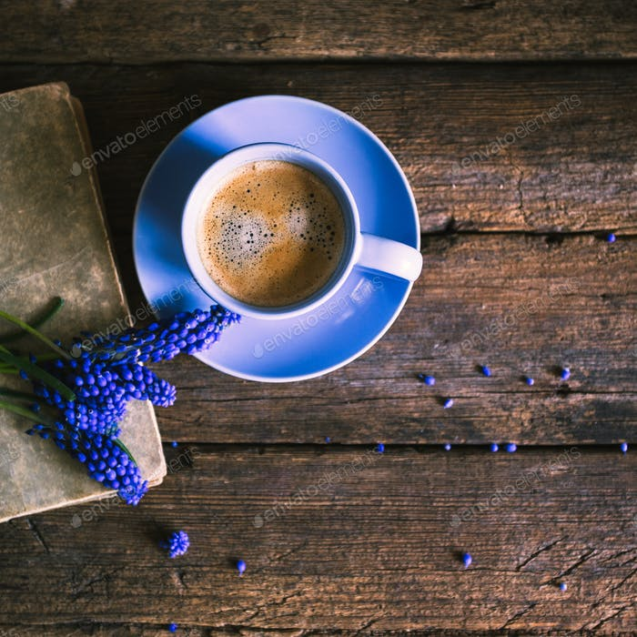 Blue flowers and a cup of coffee with a book on a wooden backgro