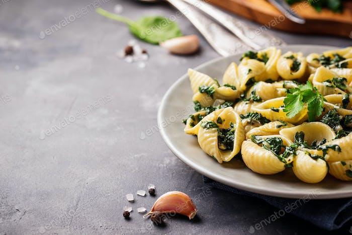 Conchiglioni pasta with spinach in creamy sauce