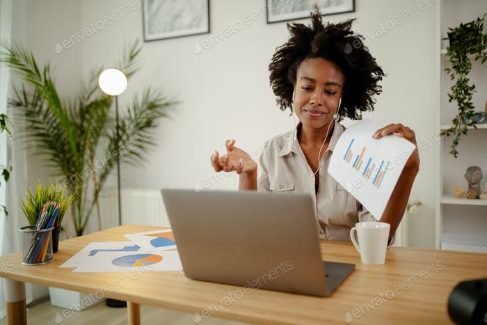 Businesswoman holding documents with financial statistic.