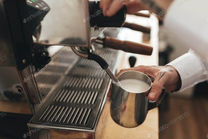 Close up man hand whipping milk for coffee by coffee machine in restaurant