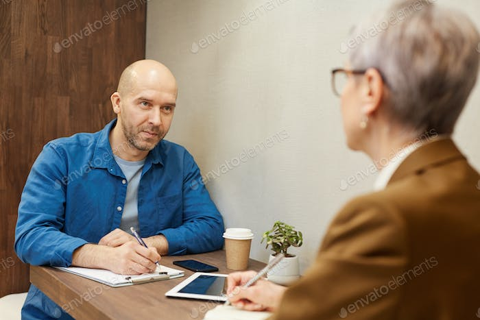 Bald Man In Business Meeting at Cafe Table