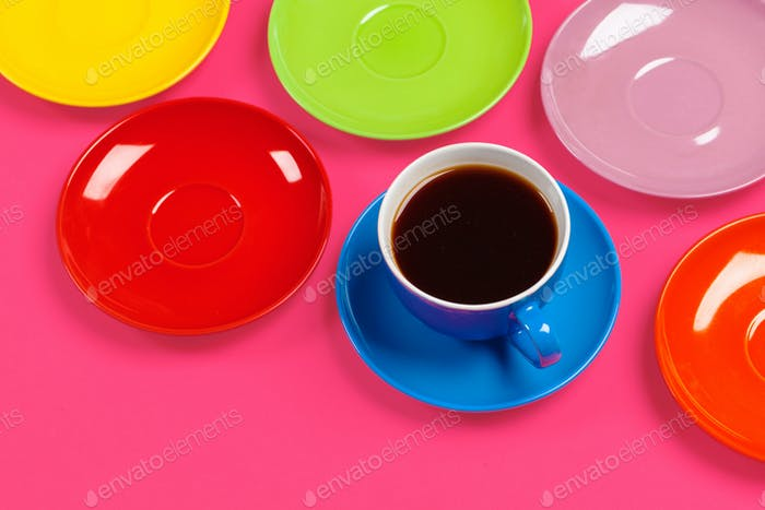 Colorful coffee cups and saucers on colorful vibrant background