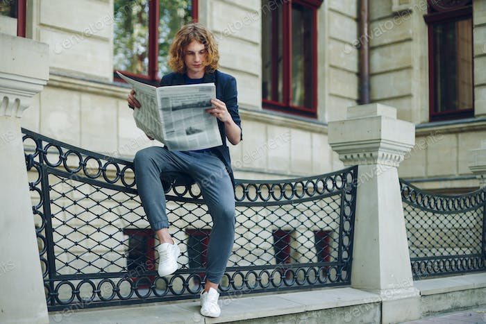 Attractive man reading newspaper near old style building