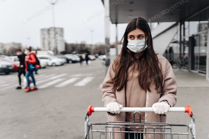 Young woman wearing protection face mask against coronavirus 2019-nCoV pushing a shopping cart