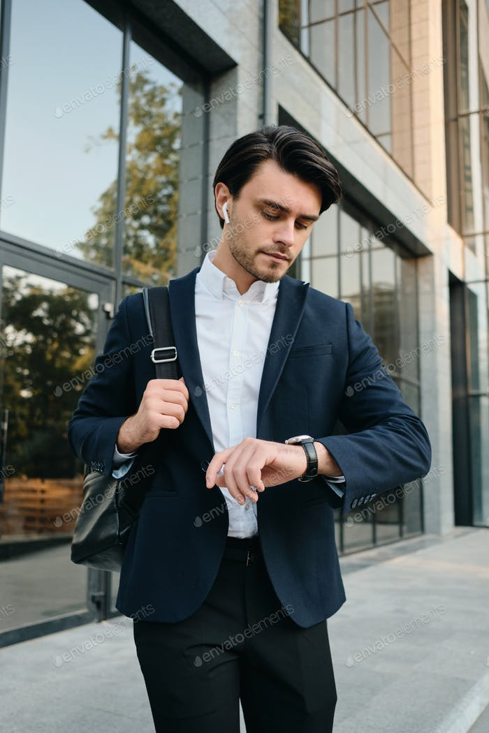Young man in classic suit with wireless earphones and backpack thoughtfully looking on watch outdoor