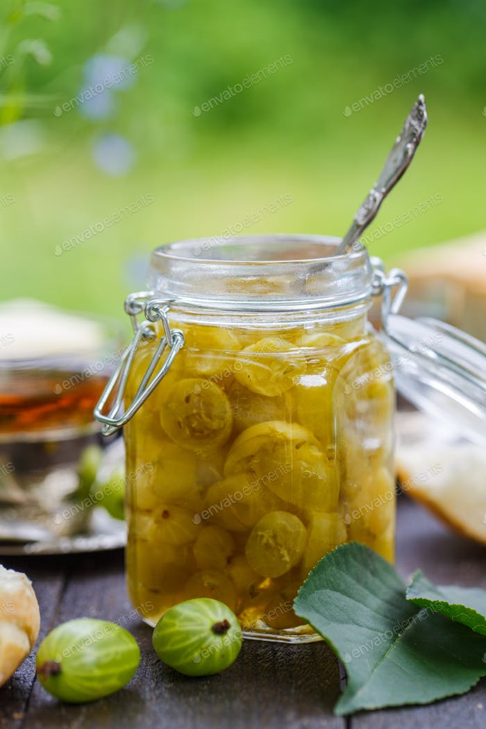 Close view of gooseberry jam in a jar on a wooden table